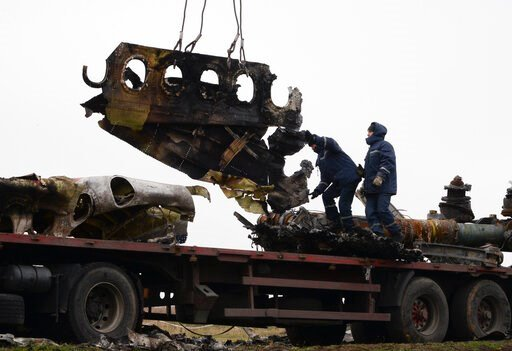 (AP Photo/Mstyslav Chernov, FILE). FILE - In this file photo dated Sunday, Nov. 16, 2014, recovery workers in rebel-controlled eastern Ukraine load debris from the crash site of Malaysia Airlines Flight 17, in Hrabove, Ukraine, with recovery operations...