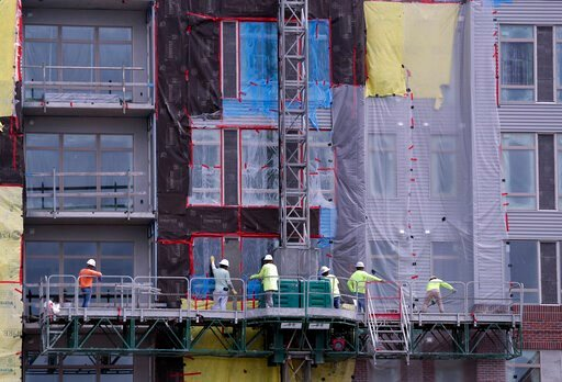 (AP Photo/John Raoux). In this June 14, 2019 photo, construction workers perform tasks on an apartment building in Orlando, Fla. On Wednesday, July 17, the Commerce Department reports on U.S. home construction in June.