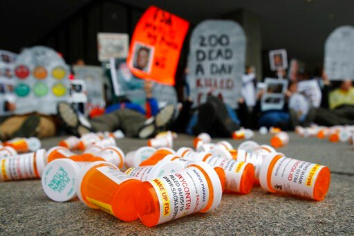 (AP Photo/Patrick Semansky, File). FILE - In this April 5, 2019, file photo, containers depicting OxyContin prescription pill bottles lie on the ground in front of the Department of Health and Human Services' headquarters in Washington as protesters de...