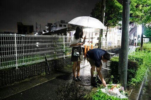 """(AP Photo/Jae C. Hong). A couple places flowers near the Kyoto Animation building, Friday, July 19, 2019, background left, that was destroyed in an arson attack in Kyoto, Japan.  A man screaming """"You die!"""" burst into an animation studio in Kyoto, douse..."""