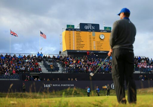 (AP Photo/Jon Super). Tiger Woods of the United States prepares to chip onto the 18th green, as the scoreboard shows the leading players and Woods score been at bottom left, during the first round of the British Open Golf Championships at Royal Portrus...