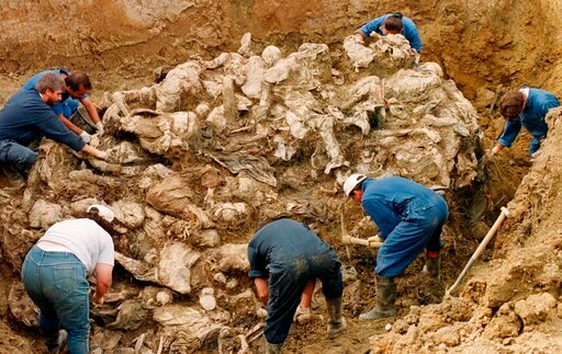 (AP Photo/Staton R. Winter, File). FILE - In this Sept. 18, 1996 file photo, International War Crimes Tribunal investigators clear away soil and debris from dozens of Srebrenica victims buried in a mass grave near the village of Pilica, some 55 kms (32...
