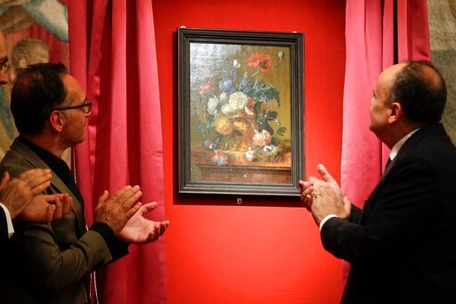 """(AP Photo/Gregorio Borgia). German Foreign Minister Heiko Mass, left, and Italian Culture Minister Alberto Bonisoli watch the unveiling of the """"Vase of Flowers"""" painting by Jan van Huysum, at the Pitti Palace, part of the Uffizi Galleries, in Florence,..."""