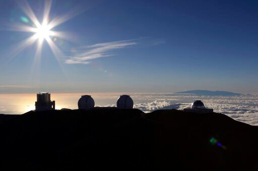 (AP Photo/Caleb Jones, File). FILE - In this Sunday, July 14, 2019, file photo, the sun sets behind telescopes at the summit of Mauna Kea. Scientists are expected to explore fundamental questions about our universe when they use a giant new telescope p...