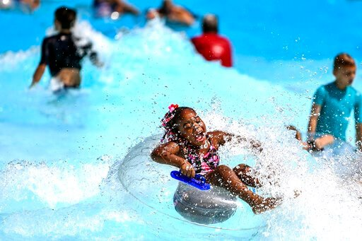 (Alexandra Wimley/Pittsburgh Post-Gazette via AP). Destinee Lucas, 6, of Aliquippa, Pa., rides a wave at the pool at Settlers Cabin Park, Thursday, July 18, 2019, in Robinson, Pa. Communities nationwide are bracing for a record-breaking heatwave that's...