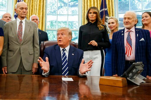 (AP Photo/Alex Brandon). President Donald Trump, accompanied by Apollo 11 astronauts Michael Collins, left, and Buzz Aldrin, right, with Vice President Mike Pence and first lady Melania Trump, speaks during a photo opportunity commemorating the 50th an...