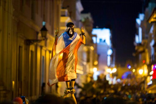 (AP Photo/Dennis M. Rivera Pichardo). A demonstrator with a Puerto Rican flag reacts during clashes in San Juan, Puerto Rico, Wednesday, July 17, 2019. Thousands of people marched to the governor's residence in San Juan on Wednesday chanting demands fo...