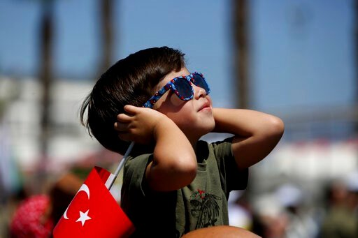(AP Photo/Petros Karadjias). A boy holding a Turkish flag watches as Turkish acrobatic jets fly, during a military parade celebration marking the 45th anniversary of the 1974 Turkish invasion in the Turkish occupied area of the divided capital Nicosia,...