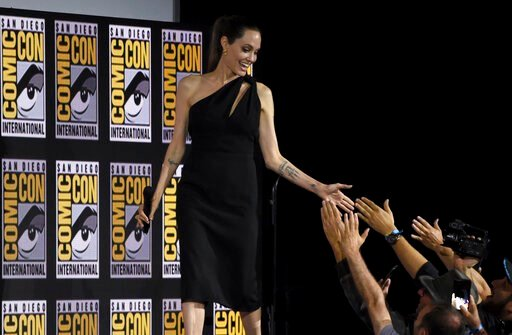 (Photo by Chris Pizzello/Invision/AP). Angelina Jolie greets fans as she walks on stage at the Marvel Studios panel on day three of Comic-Con International on Saturday, July 20, 2019, in San Diego.