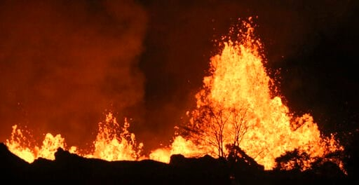 (AP Photo/Caleb Jones, File). FILE - In this May 20, 2018 file photo, lava from an open fissure on Kilauea volcano shoots high above a tree in Pahoa, Hawaii. A small pond of water has been discovered inside the summit crater of Hawaii's Kilauea volcano...