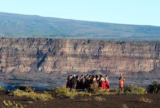 (AP Photo/Caleb Jones, File). FILE - In this April 25, 2019 photo, a group of Native Hawaiians stand next to the collapsed caldera floor of Kilauea volcano in Hawaii Volcanoes National Park on the Big Island. A small pond of water has been discovered i...