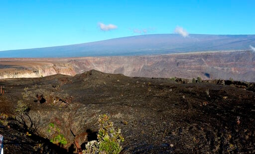 (AP Photo/Caleb Jones, File). FILE - In this April 25, 2019 file photo, the collapsed caldera floor and Halemaumau crater are shown on Kilauea volcano in Hawaii Volcanoes National Park on the Big Island. A small pond of water has been discovered inside...