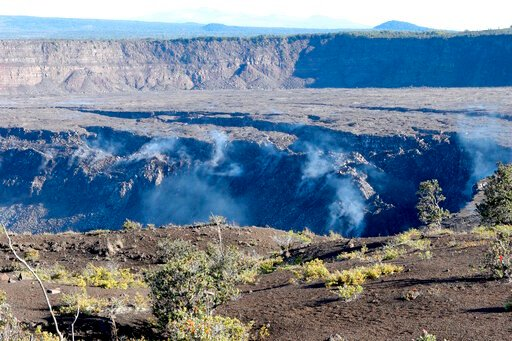 (AP Photo/Caleb Jones, File). FILE - In this April 25, 2019 photo, gas rises from the collapsed caldera floor of Kilauea volcano in Hawaii Volcanoes National Park on the Big Island. A small pond of water has been discovered inside the summit crater of ...