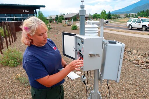 (AP Photo/Felicia Fonseca). FILE - In this Friday, July 26, 2019, photo, Anita Thompson, a forester with the Apache-Sitgreaves National Forest in eastern Arizona, checks an air quality monitor outside an emergency operations center in Flagstaff, Ariz. ...