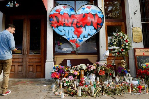 (AP Photo/John Minchillo, File). FILE - In this Aug. 7, 2019 file photo, a pedestrian passes a makeshift memorial for the slain and injured victims of a mass shooting that occurred in the Oregon District early Sunday morning in Dayton, Ohio. Ever since...