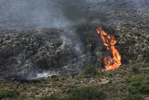 (AP Photo/Nikolia Apostolou). Firefighters approach a wildfire at Elafonisos island, south of Peloponnese peninsula, on Saturday, Aug. 10, 2019. A wildfire which broke out on Elafonisos island in southern Greece on Saturday has prompted the evacuation ...