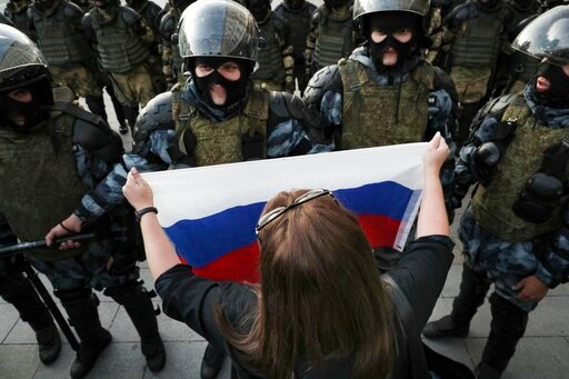(AP Photo). A woman holds a Russian national flag in front of police during a protest in Moscow, Russia, Saturday, Aug. 10, 2019. some thousands of people rallied in central Moscow for the third consecutive weekend to protest the exclusion of oppositio...
