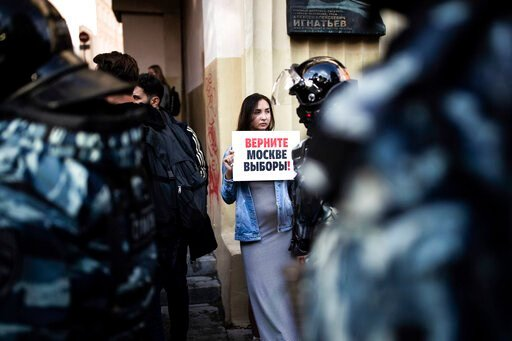 """(Evgeny Feldman, Meduza via AP). A woman holds a poster reading """"Give us back our elections in Moscow!"""" in front of police during a protest in Moscow, Russia, Saturday, Aug. 10, 2019. Some thousands of people rallied Saturday against the exclusion of s..."""
