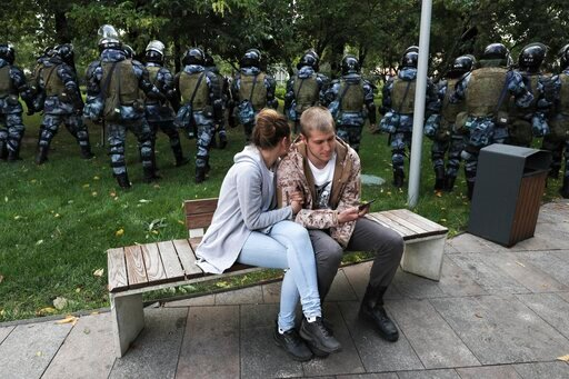 (AP Photo). A couple sit in a boulevard as police walk to prevent protesters during a rally in Moscow, Russia, Saturday, Aug. 10, 2019. Tens of thousands of people rallied in central Moscow for the third consecutive weekend to protest the exclusion of ...