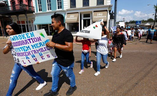 (AP Photo/Rogelio V. Solis). FILE - In this Aug. 11, 2019 photo, children of mainly Latino immigrant parents hold signs in support of them and those individuals picked up during an immigration raid at a food processing plant in Canton, Miss., following...