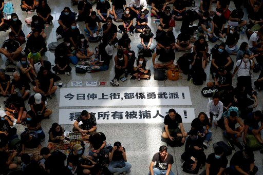 "(AP Photo/Vincent Thian). THIS ADDS TO CLARIFY THE TRANSLATION - Protesters surround banners that read: ""Those on the street today are all warriors!"" top, and ""Release all the detainees!"" during a sit-in rally at the arrival hall of the Hong Kong Inter..."
