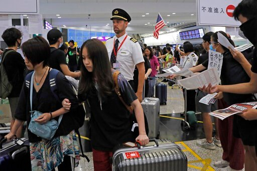 (AP Photo/Kin Cheung). Passengers and flight crew arrive at Hong Kong International Airport, Monday, Aug. 12, 2019. One of the world's busiest airports canceled all flights after thousands of Hong Kong pro-democracy protesters crowded into the main ter...