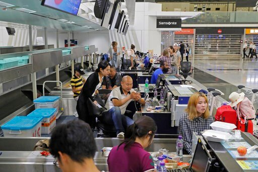 (AP Photo/Kin Cheung). Stranded travelers sit in the check-in counters at the Hong Kong International Airport, Monday, Aug. 12, 2019. One of the world's busiest airports canceled all flights after thousands of Hong Kong pro-democracy protesters crowded...
