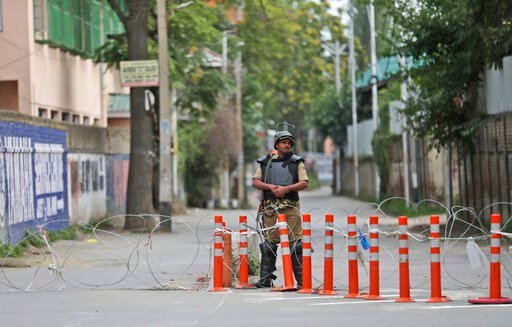 (AP Photo/Mukhtar Khan). A security person stands guard during a security lockdown in Srinagar, Indian controlled Kashmir, Monday, Aug. 12, 2019. Troops in India-administered Kashmir allowed some Muslims to walk to local mosques alone or in pairs to pr...