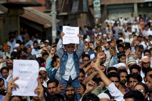 (AP Photo/ Dar Yasin). A Kashmiri Muslim boy holds a placard as others shout slogans during a protest after Eid prayers in Srinagar, Indian controlled Kashmir, Monday, Aug. 12, 2019. Troops in India-administered Kashmir allowed some Muslims to walk to ...