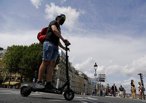 (AP Photo/Lewis Joly). A man rides an electric scooter in Paris, Monday, Aug. 12, 2019. The French government is meeting with people who've been injured by electric scooters as it readies restrictions on vehicles that are transforming the Paris citysca...