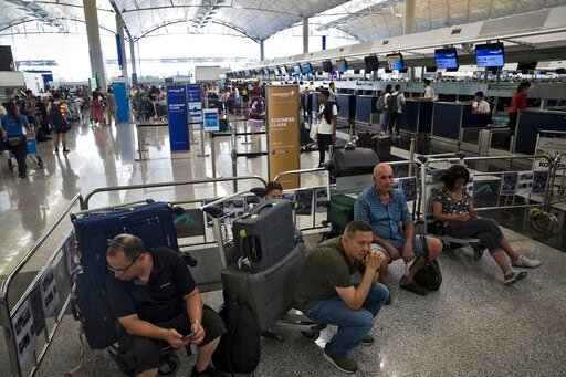 (AP Photo/Vincent Thian). Travelers wait at the check-in counters in the departure hall of the Hong Kong International Airport in Hong Kong, Tuesday, Aug. 13, 2019. Protesters clogged the departure area at Hong Kong's reopened airport Tuesday, a day af...
