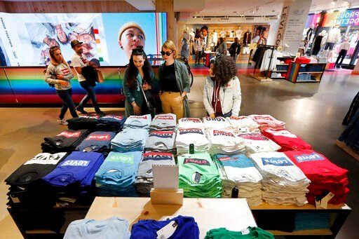 (AP Photo/Richard Drew, File). FILE- In this June 14, 2019, file photo a pair of shoppers, center, in the Levi's store in New York's Times Square, survey a T-shirt display. On Tuesday, Aug. 13, the Labor Department reports on U.S. consumer prices for J...