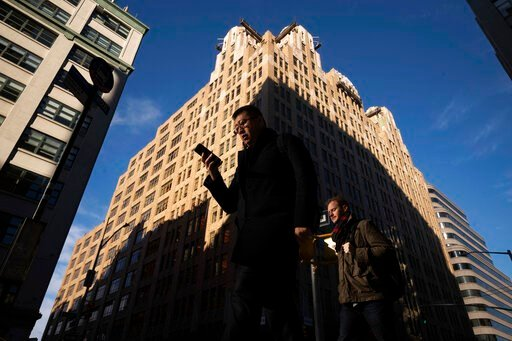 (AP Photo/Mark Lennihan, File). FILE - In this Dec. 17, 2018, file photo people walk by a building in New York. You carry your smartphone everywhere. But the way you use it could leave you vulnerable to specific forms of identity theft, including roboc...