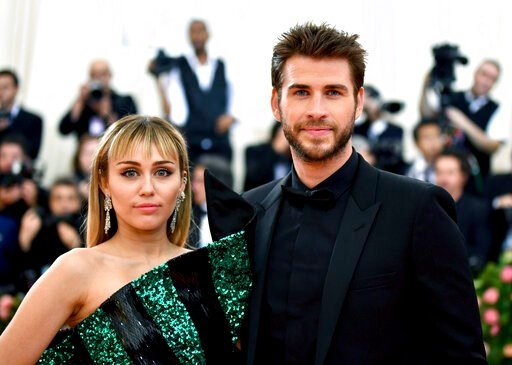 "(Photo by Charles Sykes/Invision/AP, File). FILE - In this May 6, 2019 file photo, Miley Cyrus, left, and Liam Hemsworth attend The Metropolitan Museum of Art's Costume Institute benefit gala celebrating the opening of the ""Camp: Notes on Fashion"" exhi..."