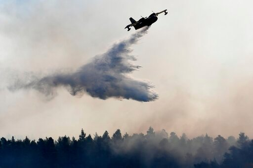 (AP Photo/Michael Varaklas). An airplane drops water over a wildfire near Halkida town on the Greek island of Evia, Wednesday, Aug. 14, 2019. More than a thousand firefighters battled wildfires Tuesday in Greece, with the largest burning out of control...