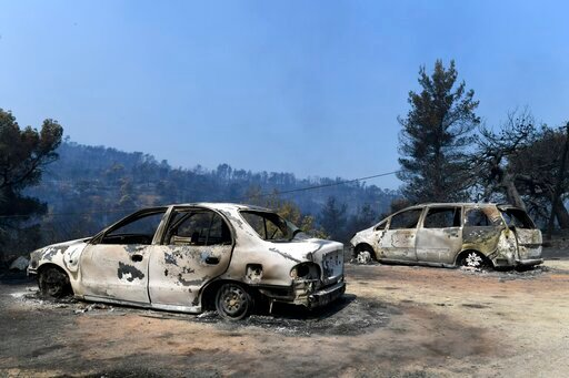 (AP Photo/Michael Varaklas). Burned cars are seen after a wildfire in Makrymalli village on the Greek island of Evia, Wednesday, Aug. 14, 2019. Water-dropping planes and helicopters have resumed work at first light over a major wildfire burning through...