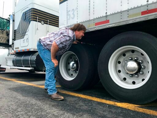 (AP Photo/Tom Sampson). In this June 13, 2019 photo, truck driver Terry Button looks over his trailer during at stop in Opal, Va. The Trump administration has moved a step closer to relaxing federal regulations governing the amount of time truck driver...