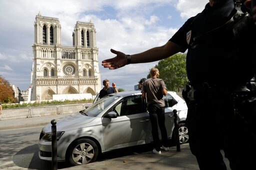 (AP Photo/Lewis Joly). Police officers clear the area around Notre Dame cathedral in Paris, Monday, Aug. 12, 2019. Authorities started clearing the area around Notre Dame ahead of decontamination and cleanup work which will resume on Aug. 19 after new ...