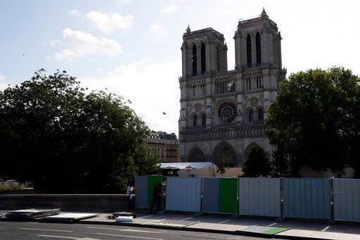 (AP Photo/Francois Mori). Workers install high fences on a bridge around Notre Dame cathedral in Paris, Tuesday, Aug. 13, 2019. Workers are preparing to decontaminate some Paris streets surrounding the Notre Dame Cathedral that have been tested with hi...