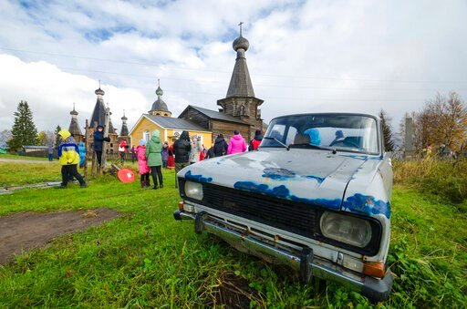 (AP Photo/Sergei Yakovlev). In this photo taken on Oct. 7, 2018, people walk the street with the 18th century Trinity Church in the background in the village of Nyonoksa, northwestern Russia. The Aug. 8, 2019, explosion of a rocket engine at the Russia...