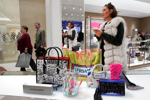 (AP Photo/Mark Lennihan, File). FILE - In this March 14, 2019 file photo a woman shops at Neiman Marcus during the opening night of The Shops & Restaurants at Hudson Yards in New York. Retailers and consumer product makers like American Textile may...