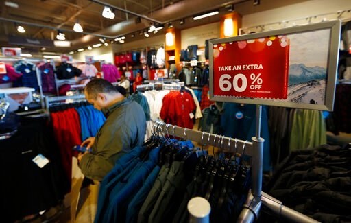 (AP Photo/David Zalubowski, File). FILE - In this Dec. 24, 2018, photo a last-minute shopper scans his mobile device next to a sign marking discounts on coats at Columbia store at the Outlet Malls in Castle Rock in Castle Rock, Colo. Retailers and cons...