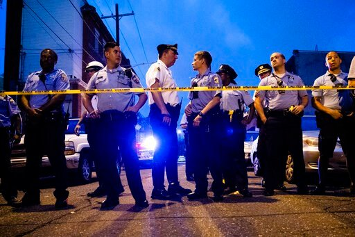 (AP Photo/Matt Rourke). Officers gather for crowd control near a massive police presence set up outside a house as they investigate a shooting in Philadelphia, Wednesday, Aug. 14, 2019.