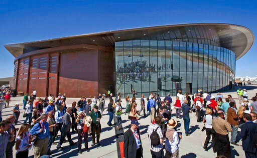 (AP Photo/Matt York, File). FILE - In this Oct. 17, 2011 file photo, guests stand outside the new Spaceport America hangar in Upham, N.M. Virgin Galactic is scheduled to unveil the interior of its digs at Spaceport America, providing the first glimpse ...