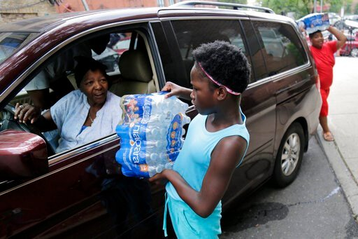 (AP Photo/Seth Wenig). Elaine Younger, 11, and Tahvion Williams, 14, right, load water in their family's van at the Newark Health Department in Newark, N.J., Wednesday, Aug. 14, 2019. Residents began picking up bottled water on Monday, days after eleva...