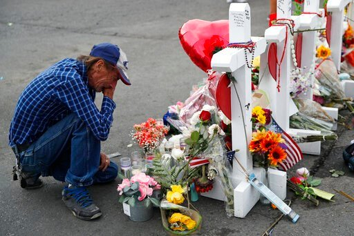 (AP Photo/John Locher, File). FILE - In this Aug. 6, 2019 file photo, Antonio Basco cries beside a cross at a makeshift memorial near the scene of a mass shooting at a shopping complex, in El Paso, Texas. Basco, whose 63-year-old wife was among the Tex...