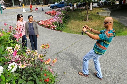 (AP Photo/Dan Joling). Junar Lim takes photos of Ziah Lim, left, and Arsenia Lim, all of Cavite, the Philippines, at gardens in Town Square in Anchorage, Alaska, Thursday, Aug. 15, 2019. Alaska recorded its warmest month ever in July and hot, dry weath...