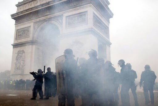 (AP Photo/Thibault Camus, File). FILE - In this Saturday, Jan. 12, 2019 file photo riot police take position around the Arc de Triomphe during clashes with yellow vest protesters, in Paris, France.
