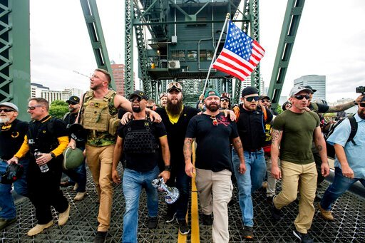 "(AP Photo/Noah Berger). Members of the Proud Boys and other right-wing demonstrators march across the Hawthorne Bridge during an ""End Domestic Terrorism"" rally in Portland, Ore., on Saturday, Aug. 17, 2019. The group includes organizer Joe Biggs, in gr..."