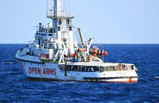 (AP Photo/Salvatore Cavalli). The Open Arms vessel with 107 migrants on board is anchored off the Sicilian vacation and fishing island of Lampedusa, southern Italy, Monday, Aug. 19, 2019. Open Arms on Monday suggested chartering a plane to fly to Spain...